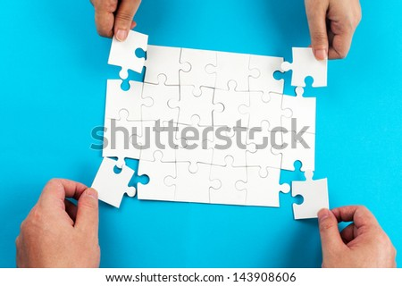 Two person holding jigsaw puzzle pieces and putting them together - stock photo