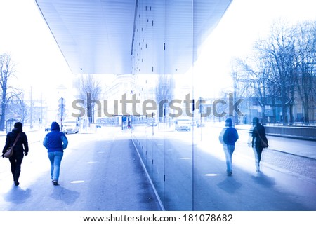 Two person moving in busy street in blue tone