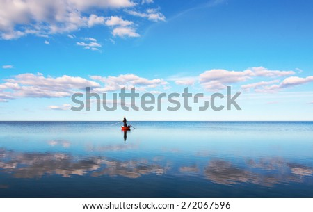Two persons in small red rowboat fishing in sea with blue sky reflected in calm water - stock photo