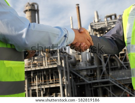 Two petrochemical engineer closing a deal in front of an oil refinery - stock photo