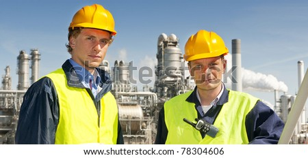 Two petrochemical engineers in front of a refinery, wearing hard hats and safety vests