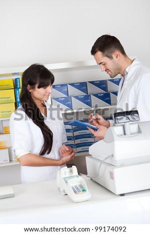 Two pharmacists checking drugs at the drugstore - stock photo