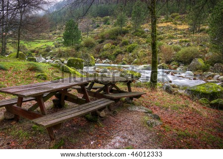 Two picnic tables in a park by the river in a cold rainy day