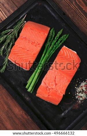 two piece of fresh raw pink salmon on black tray with rosemary and asparagus dry spices healthy food diet cooking concept