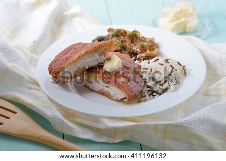 Two pieces of battered chicken fillet with a side dish of rice and mushrooms. - stock photo