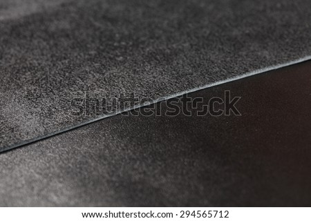 Two pieces of black leather. Nubuck and smooth  leather surface - stock photo