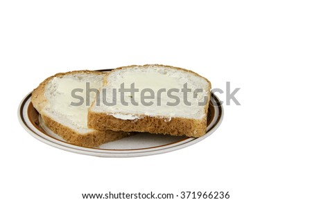 Two pieces of buttered bread on a serving plate isolated with a clipping path at original size - stock photo
