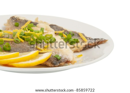 Two pieces of fried goldfish and sea slices of lemon. On a white background - stock photo