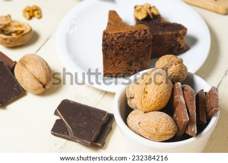 two pieces of nut cake and ingredients on aged wooden table - stock photo