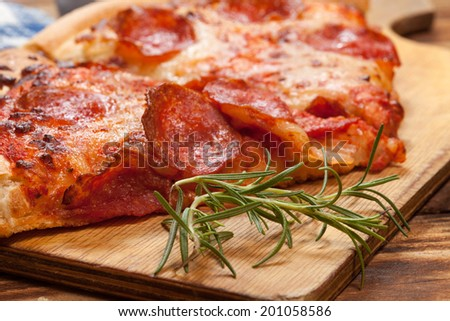 Two pieces of pizza with topping on a wooden table.