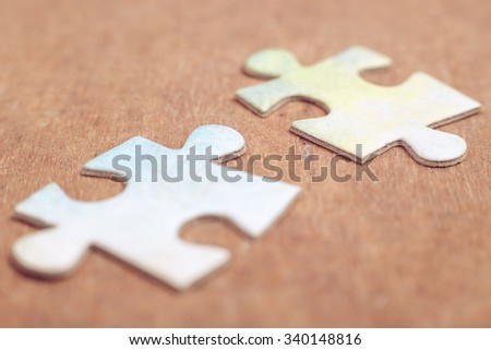 Two pieces of puzzle lying on the rustic wooden background. - stock photo