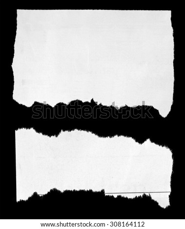 Two pieces of torn paper on black - stock photo