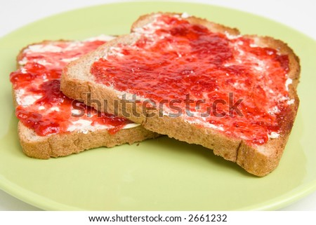 Two pieces of wheat bread toast with butter / margarine and strawberry jam sitting on a green plate. - stock photo