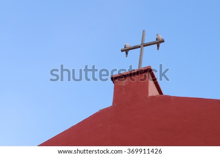 Two pigeons on the wooden cross of red church against blue sky - stock photo