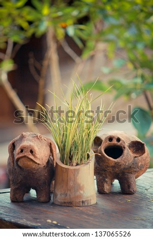 Two pigs clay decorating in the garden - stock photo