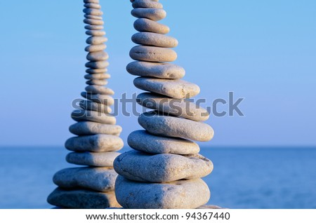 Two pile of pebbles in the balance on the seacoast - stock photo