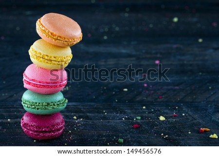 Two piles of colorful macaroons on a dark black wooden background with selective focus and small crumbs on the table - stock photo