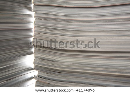 Two piles of thick old magazines, in beautiful illumination - stock photo