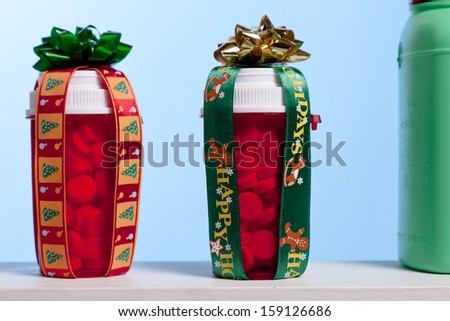 Two pills bottles with bows and ribbon sit on a shelf with with other medicine cabinet items. - stock photo