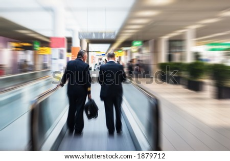 two pilots on a moving escalator - stock photo