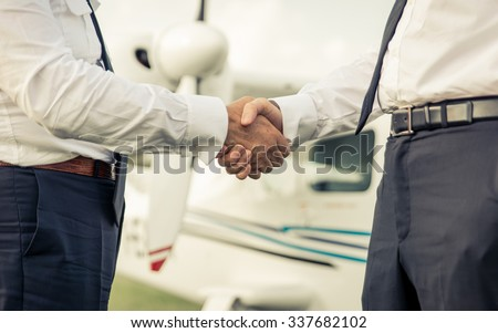 Two pilots shaking hands before the flight  - stock photo