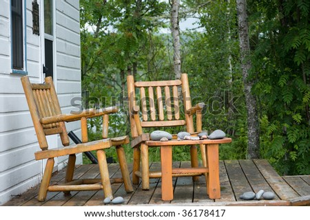 two pine log chairs on porch with stacks of gathered rocks - stock photo