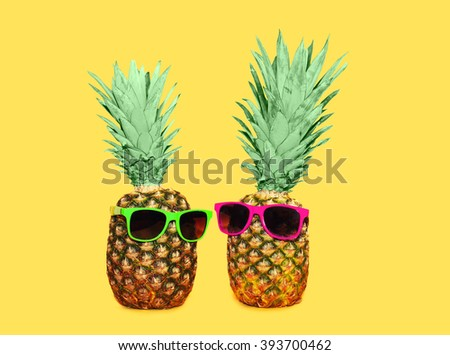 Two pineapple with sunglasses on yellow background, colorful ananas concept - stock photo