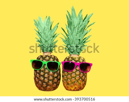 Two pineapple with sunglasses on yellow background, colorful ananas photo - stock photo