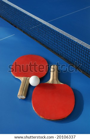 Two ping pong paddles with ball on the table - stock photo