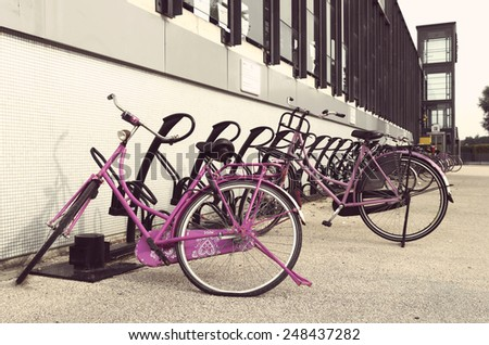 two pink bicycles parked outside a train station - stock photo