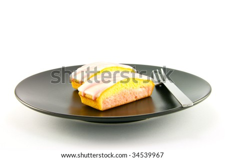 Two pink strawberry sliced cakes with icing on the top with a small fork on a black plate with a white background