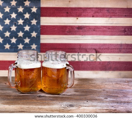 Two pint jars filled with beer with vintage wooden USA flag in background. - stock photo