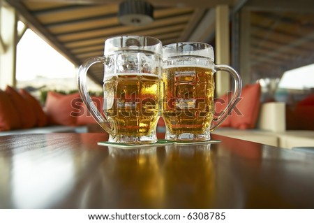 two pints of beer in cafe interior - stock photo