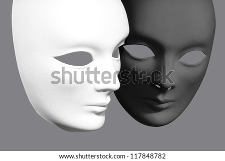 Two plaster Venetian masks on a gray background