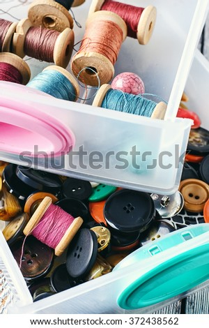Two plastic box with sewing threads and buttons. - stock photo