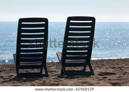 Two plastic empty chairs stand on  beach near  sea opposite  sun - stock photo