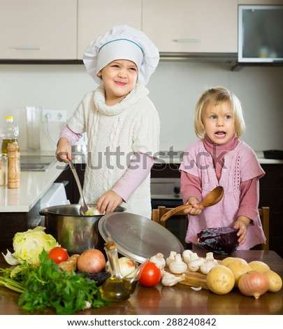 Two playful smiling little girls learning how to cook at domestic kitchen