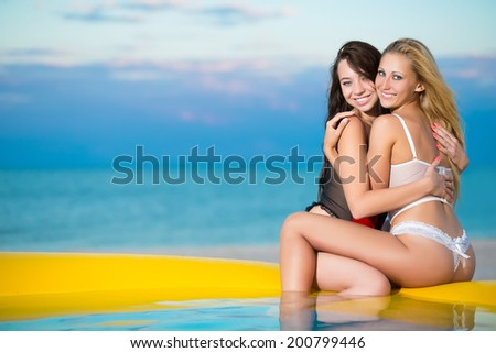 Two playful women hugging each other on the beach at sunset - stock photo