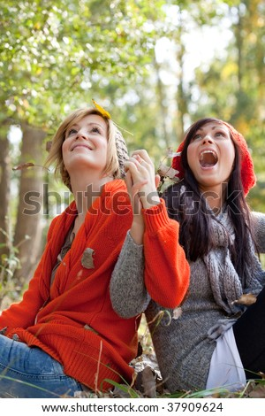 Two playing girls in forest park throwing leaves and foliages in warm winter clothes on beautiful weather day - stock photo