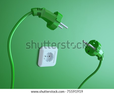 Two plugs struggle for the electric socket - stock photo