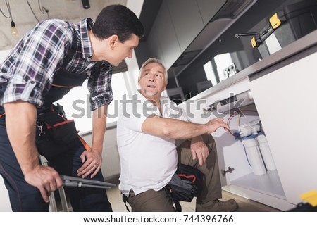 Two plumbers prepared to repair the kitchen sink. One of them is next to the pipes, the second is near and helps to choose a tool. A black toolbox is next to it.