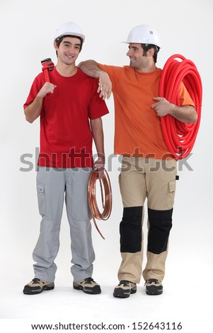Two plumbers stood together - stock photo