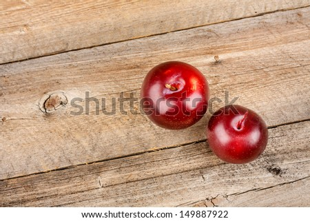 Two Plums on Wooden Table