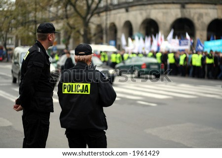 Two police officers during an anti-government demonstration in Warsaw Poland on 7 October 2006 (Blue March by Platforma Obywatelska). Purposely taken with a shallow DOF not to detail faces.