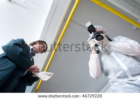 Two policemen hovering over a dead body. A police lieutenant putting on his rubber gloves, and a forensics experts taking pictures of the deceased. - stock photo