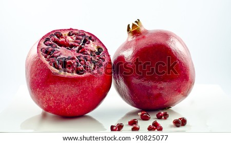Two pomegranates with scattered seeds - stock photo