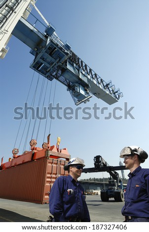 two port workers with cargo containers being hoisted by large crane - stock photo