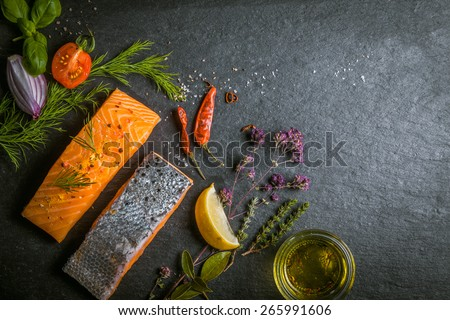 Two portions of fresh gourmet uncooked salmon fillet displayed on a slate background with herbs, olive oil chilli peppers, tomato and onion in a savory recipe, copyspace - stock photo