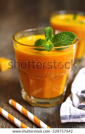 Two portions of fresh pumpkin juice with mint leaf in a glasses on a rustic wooden background.