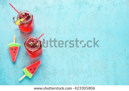 Two portions of homemade watermelon lemonade in mason jar with red striped straw and watermelon popsicles on a blue background - stock photo